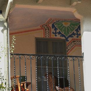 Ejemplo de fachada beige, mediterránea, pequeña, de dos plantas, con revestimiento de estuco