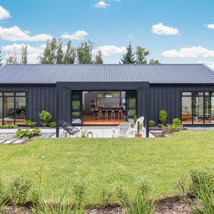 Свежая идея для дизайна: одноэтажный фасад частного дома черного цвета в стиле кантри с металлической крышей - отличное фото интерьера