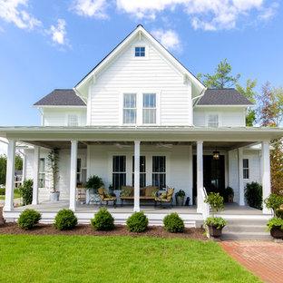 Неиссякаемый источник вдохновения для домашнего уюта: двухэтажный фасад дома белого цвета в стиле кантри с облицовкой из дерева и двускатной крышей
