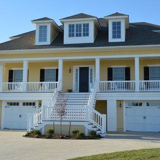 他の地域のトラディショナルスタイルのおしゃれな家の外観 (木材サイディング、黄色い外壁) の写真