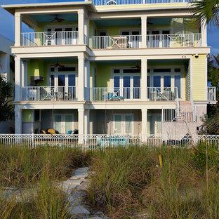 Foto de fachada de casa amarilla, exótica, grande, de tres plantas, con revestimiento de madera, tejado plano y tejado de metal