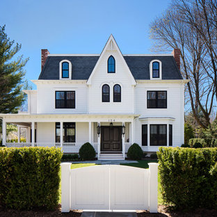 Inspiration for a large victorian white three-story vinyl house exterior remodel in New York with a shingle roof