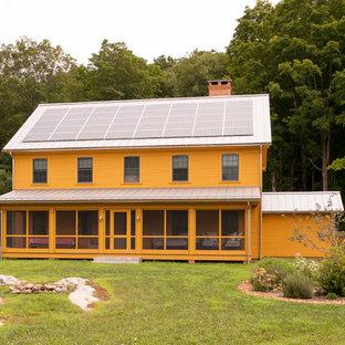 Inspiration för ett lantligt oranget hus, med två våningar och sadeltak
