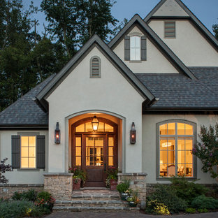 Large transitional green two-story stucco gable roof idea in Other