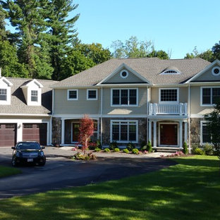 Example of a large minimalist beige two-story mixed siding gable roof design in Other