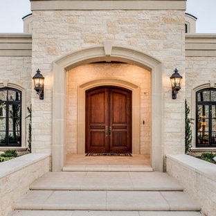 Large mediterranean beige two-story stone house exterior idea in Austin with a hip roof and a metal roof