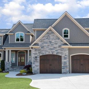 Foto della facciata di una casa unifamiliare grigia american style a due piani con rivestimenti misti, tetto a capanna e copertura a scandole