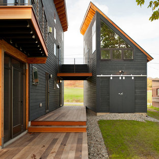 Example of a mid-sized trendy gray two-story wood house exterior design in Burlington with a shed roof and a metal roof