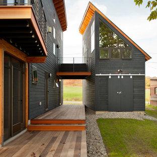 Esempio della facciata di una casa grigia contemporanea a due piani con rivestimento in legno e tetto a una falda