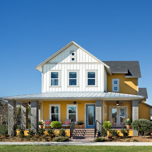 Example of a coastal yellow two-story mixed siding exterior home design in Orlando with a mixed material roof