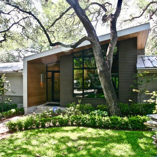 Inspiration for a mid-sized 1960s gray one-story mixed siding house exterior remodel in Austin with a shed roof and a metal roof