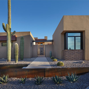 Mid-sized southwest brown one-story stucco flat roof photo in Phoenix