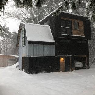 Imagen de fachada de casa negra, actual, pequeña, de dos plantas, con revestimiento de madera, tejado a doble faldón y tejado de metal
