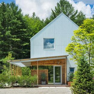 Foto de fachada de casa blanca, moderna, pequeña, de una planta, con revestimiento de metal y tejado a dos aguas