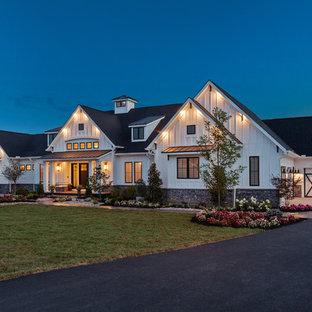 Diseño de fachada de casa blanca, campestre, extra grande, de una planta, con revestimiento de aglomerado de cemento y tejado de teja de madera