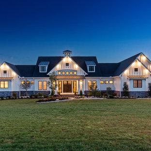 Foto della facciata di una casa unifamiliare ampia bianca country a un piano con rivestimento con lastre in cemento e copertura a scandole