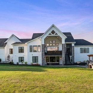 Cette photo montre une très grande façade de maison blanche nature à un étage avec un revêtement en panneau de béton fibré et un toit en shingle.