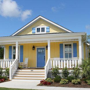 Esempio della facciata di una casa piccola gialla stile marinaro a due piani con rivestimento in legno e tetto a capanna
