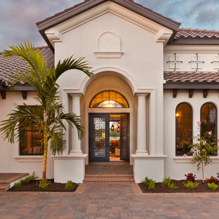 Huge mediterranean white one-story stucco house exterior idea in Tampa with a hip roof and a shingle roof