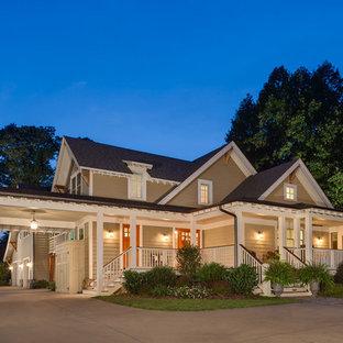 Modelo de fachada beige, de estilo americano, grande, a niveles, con revestimiento de aglomerado de cemento