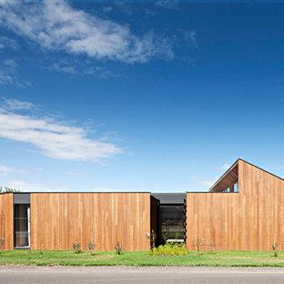 Foto della facciata di una casa unifamiliare marrone moderna a un piano con rivestimento in legno e tetto piano