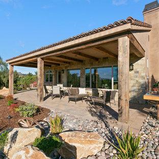 Diseño de fachada de casa marrón, mediterránea, de una planta, con revestimiento de piedra y tejado de teja de barro