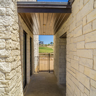 Large country one-storey white house exterior in Austin with stone veneer, a shed roof and a metal roof.