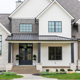 Modelo de fachada de casa blanca, clásica renovada, grande, de dos plantas, con revestimientos combinados, tejado a dos aguas y tejado de teja de madera