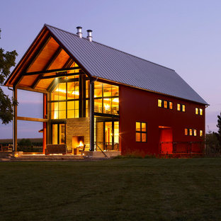 Example of a farmhouse red gable roof design in Milwaukee
