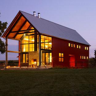 Immagine della facciata di una casa rossa country con tetto a capanna