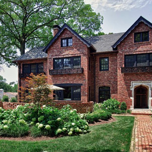 Example of a classic red three-story brick exterior home design in St Louis
