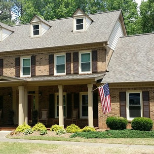 Large transitional brown two-story concrete exterior home photo in Atlanta with a shingle roof