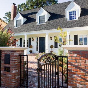 Diseño de fachada blanca, clásica, de tamaño medio, de dos plantas, con revestimiento de madera y tejado a dos aguas