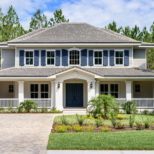 Example of a large beach style multicolored two-story mixed siding house exterior design in Jacksonville with a hip roof and a shingle roof