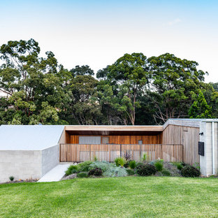 Modern split-level concrete grey house exterior in Gold Coast - Tweed with a flat roof and a metal roof.