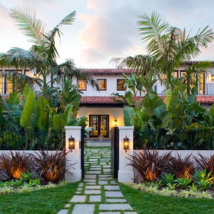 Inspiration for a mediterranean white two-story exterior home remodel in Los Angeles with a hip roof and a tile roof