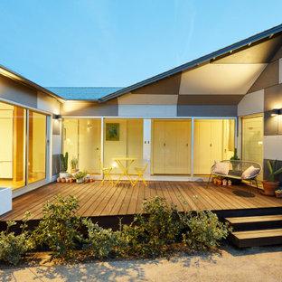 Idee per la villa grigia moderna a un piano con rivestimento in cemento, tetto a padiglione e copertura a scandole