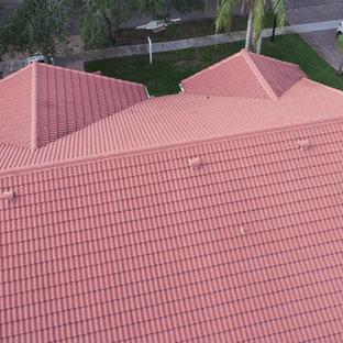 Immagine della facciata di una casa unifamiliare gialla classica a un piano di medie dimensioni con rivestimento in stucco, tetto a capanna e copertura in tegole