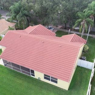 Idee per la facciata di una casa unifamiliare gialla classica a un piano di medie dimensioni con rivestimento in stucco, tetto a capanna e copertura in tegole