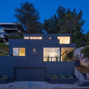 Diseño de fachada de casa negra, moderna, de tamaño medio, de tres plantas, con revestimiento de aglomerado de cemento, tejado plano y techo verde