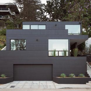 Foto på ett mellanstort funkis svart hus, med tre eller fler plan, fiberplattor i betong, platt tak och levande tak