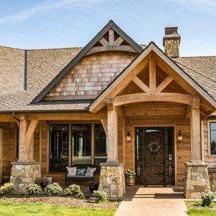 Imagen de fachada de casa marrón, rural, grande, de una planta, con revestimiento de piedra, tejado a dos aguas y tejado de teja de madera