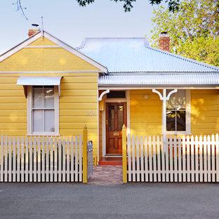 Modelo de fachada de casa amarilla, clásica, de tamaño medio, de una planta, con revestimiento de madera, tejado a dos aguas y tejado de metal