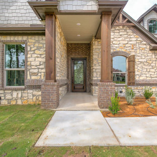 Inspiration for a french country brown one-story stone house exterior remodel in Dallas with a hip roof and a shingle roof