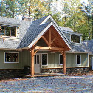 Imagen de fachada de casa verde, rústica, grande, de dos plantas, con revestimiento de piedra, tejado a dos aguas y tejado de teja de madera