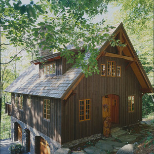 Ejemplo de fachada marrón, rústica, pequeña, de tres plantas, con revestimiento de madera y tejado a dos aguas