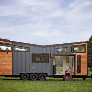 Стильный дизайн: одноэтажный, разноцветный мини-дом в современном стиле с комбинированной облицовкой и крышей-бабочкой - последний тренд