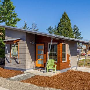 Inspiration för små moderna grå trähus, med allt i ett plan, pulpettak och tak i metall