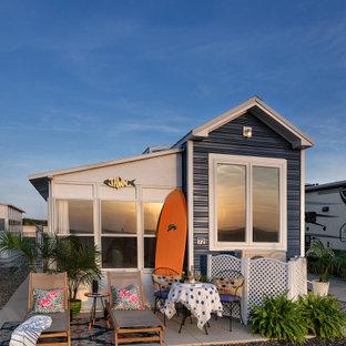 Пример оригинального дизайна: маленький, двухэтажный, синий мини-дом в морском стиле с облицовкой из металла, вальмовой крышей и металлической крышей