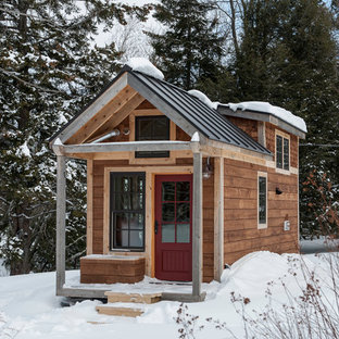 This is an example of a small rustic two floor tiny house in Burlington with wood cladding and a pitched roof.